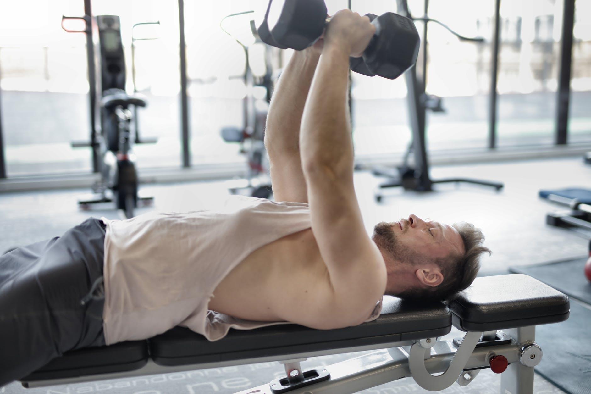man på træningsbænk i fitnesscenter