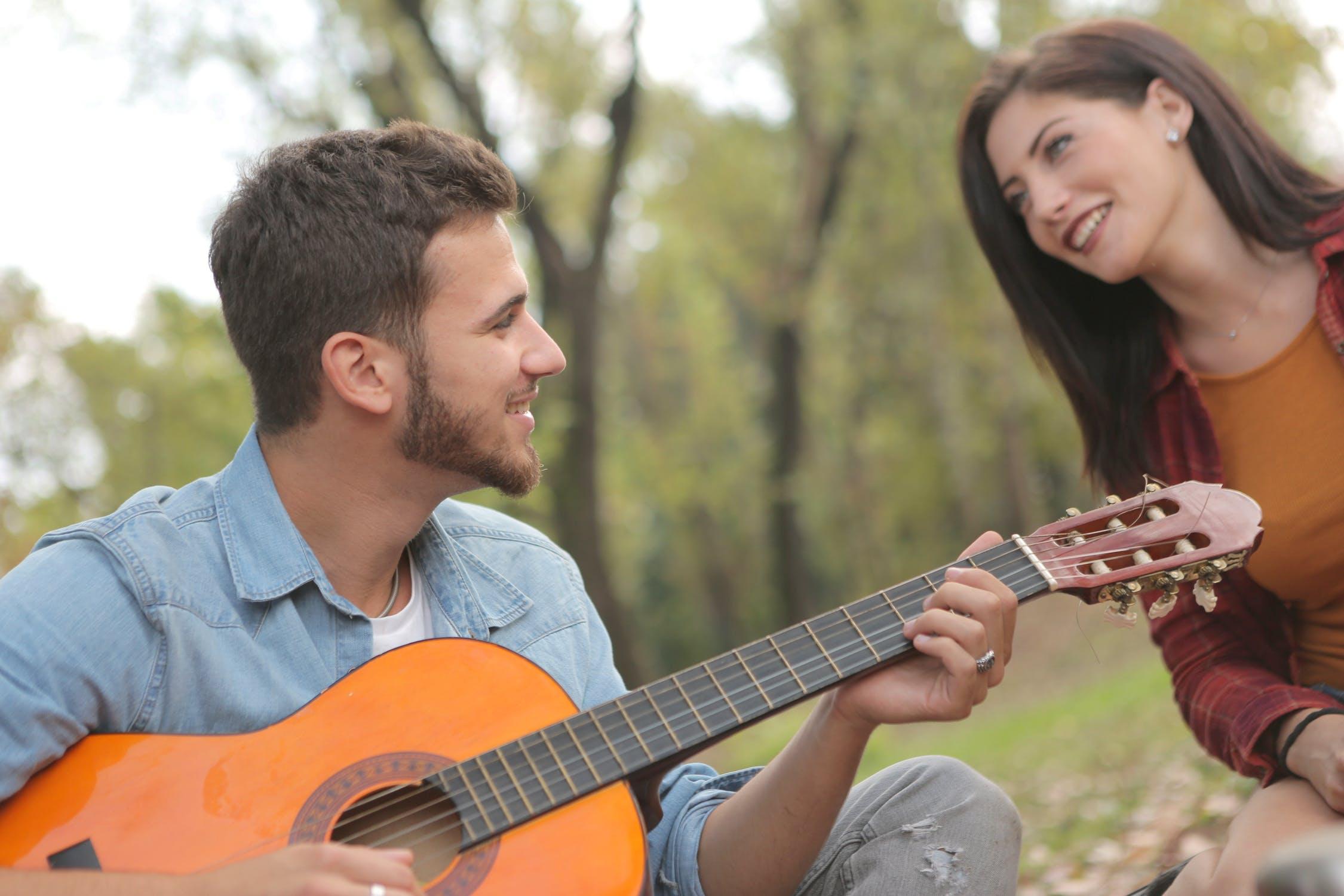 Mand spiller guitar for kvinde
