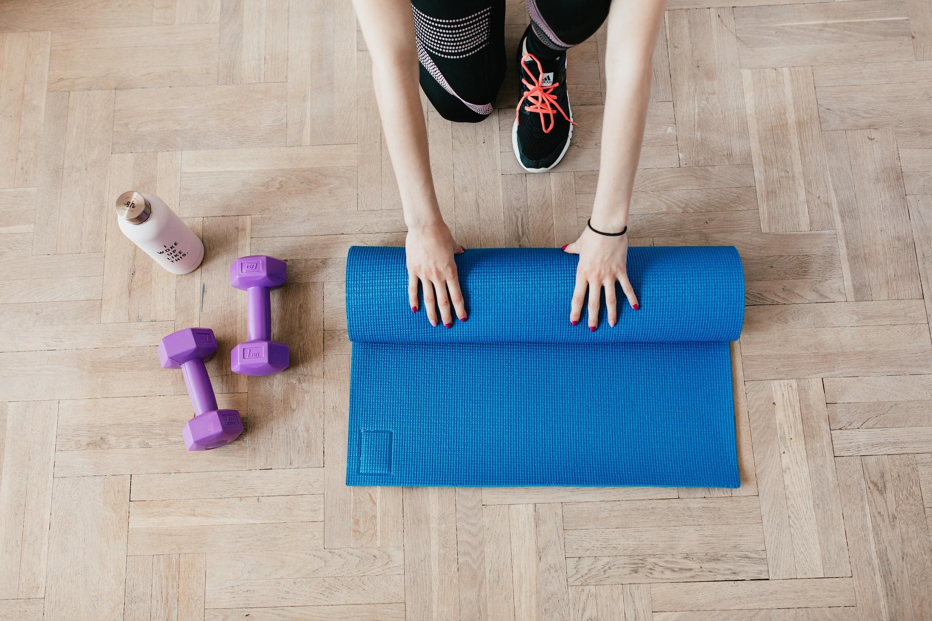 Kvinde ruller yogamåtte