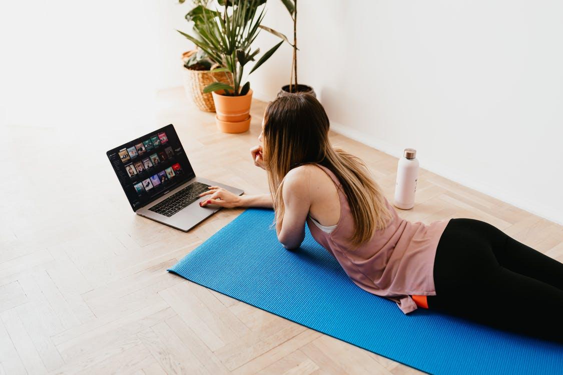 Liggende kvinde på yogamåtte med computer
